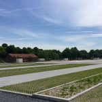 Groene parkeerplaatsen in een dambordpatroon en toegangsweg in klinkers (juni 2016)